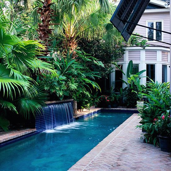 Back Yard -  We love having a pool, but with the kids older now the lap pool would be ideal. My favorite feature of the pool is the waterfall.  This lush palm tree backdrop is pretty and low-maintainance, definately a plus. The uplighting creates beautifully interesting shadowplay. Herringbone pavers are a lovely way to finish the area. #bhg.com