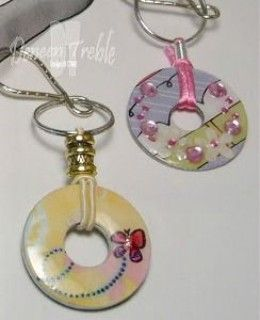 Pendant made using scrap paper and mod podge covered washers, finished with a layer of liquid glass