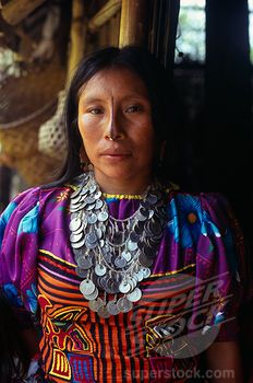 Colombia, Darien, Kuna Indigenous Tribe, Three-Quarter Portrait Of Kuna Indian Woman From The Arquia Community Wearing Traditional Mola Applique Layered Design Of Mythical Kuna Birds Gold Nose Ring With Black Line Drawn Along Length Of Nose And A Silver Necklace Of Old Colombian And Panamanian Coins. Cuna | Stock Photo #1850-24362