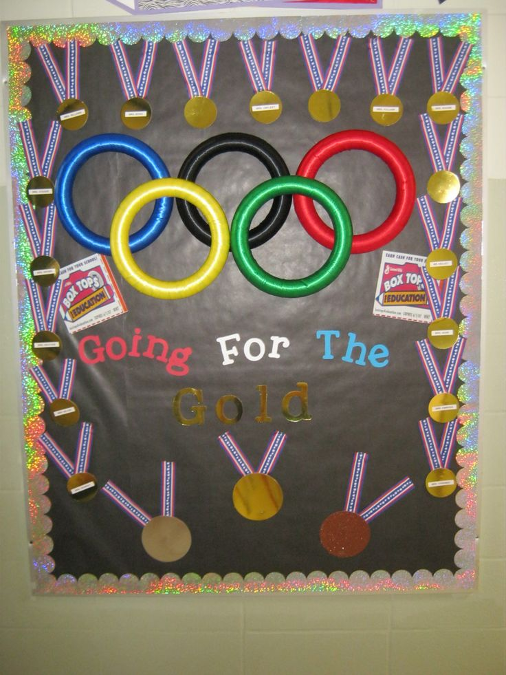 Box top Bullentin Board.  Going for the Gold.  The ribbons around the edges has each teacher name on it.  tToward the bottom is Gold, silver, and Bronze.  Each month we count a teachers medal could get moved.  we used scrapbook paper, and ribbon to make most of it.  the rings have ribbon covering foam wreath,