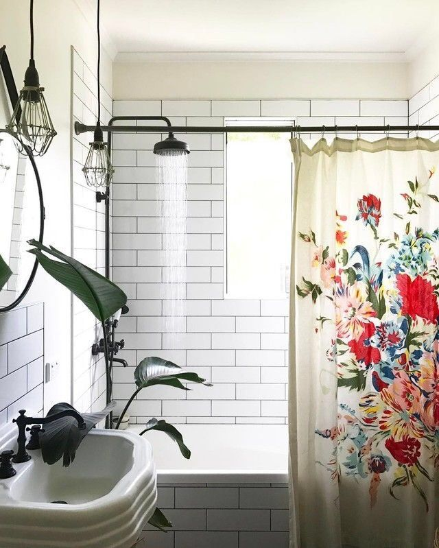Bathroom with white rectangular tile and brown hardware accented with a floral shower curtain
