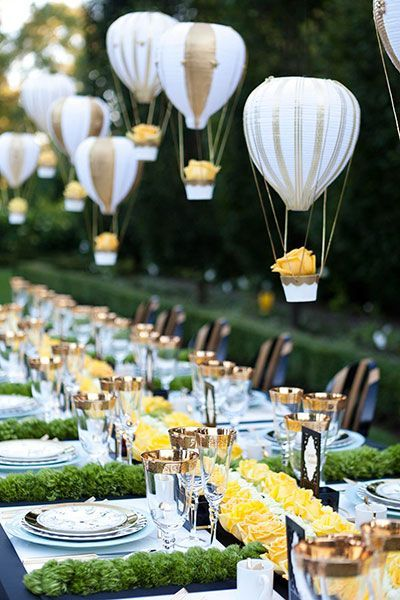 Whimsical hot air balloon centerpieces with yellow roses add fun and bright color to a wedding table