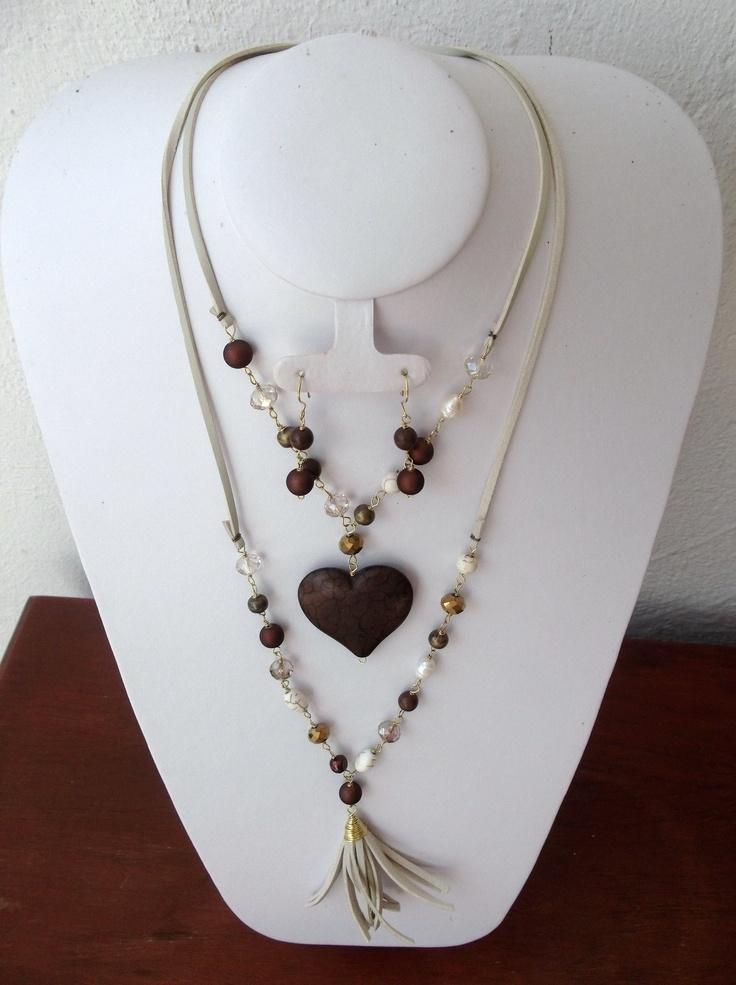 Collar montado en gamuza con cuentas color cafe y perla, con dije de corazon de piedra natural..