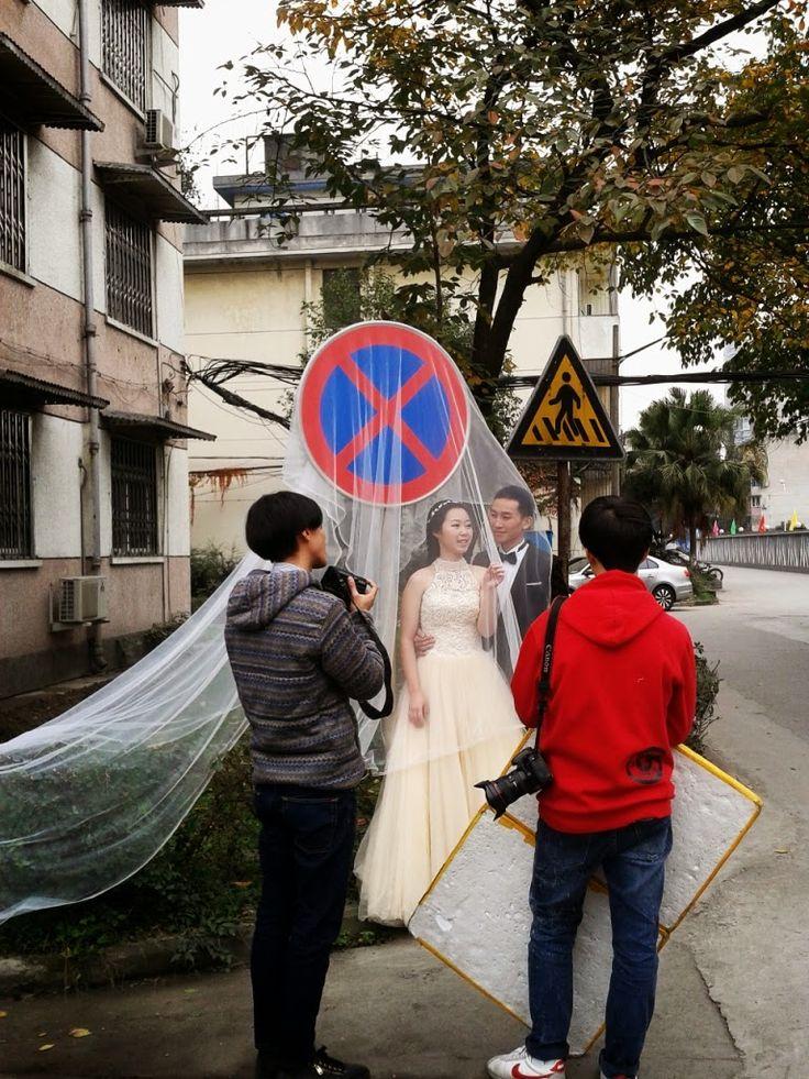 Ślubna sesja zdjęciowa w Chinach. Pełna absurdu, dziwna, w tle znak drogowy, a na nim rozwieszony welon panny młodej. Na zasadzie żyli długo i szczęśliwie..