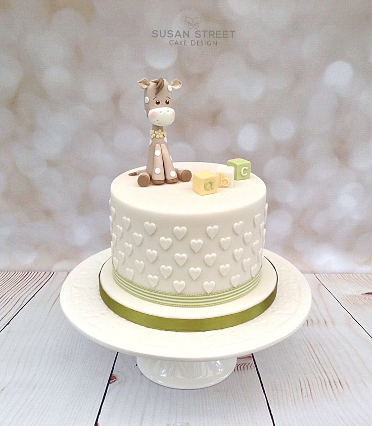 'New Baby' announcement cake. Ivory and lime green with cute baby giraffe