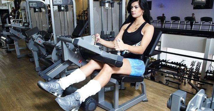 A cadeira flexora está no treino da coelhinha da Playboy para definir os músculos posteriores de coxa. Sente-se com as costas apoiadas no aparelho e mantenha o calcanhar em cima do rolo de peso. O suporte deve ficar bem próximo da coxa