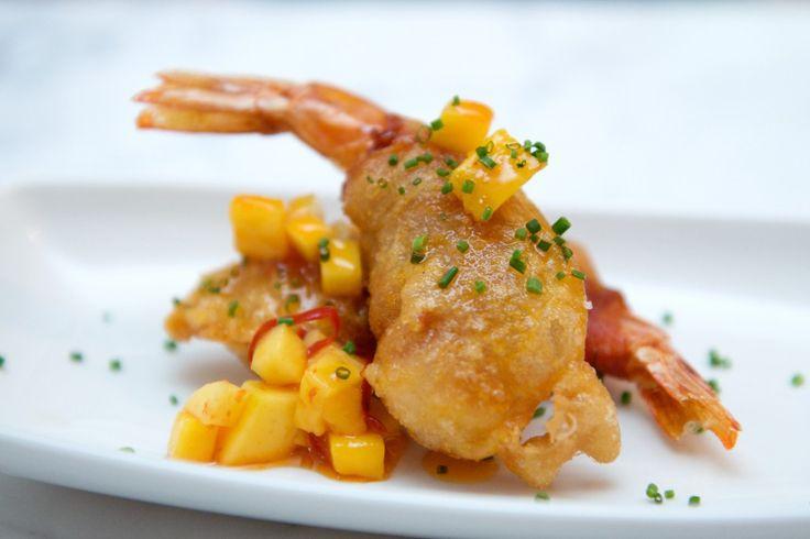 """Le acidità in cucina sono un elemento chiave per valorizzare le note sapide del pesce. In questo piatto, i gamberoni rossi di Mazara de Vallo vengono serviti in una tempura calda e avvolgente, accanto a un """"cubismo"""" di mango e a una salsina piccante di miele di arancio e salsa di soia. Poesia siculo-giapponese. Scoprite la ricetta su www.frescopesce.it/gamberoni-rossi-in-tempura-con-mango-e-salsa-piccante-al-miele"""