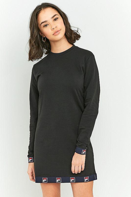 """Dieses Kleid von Fila in lässiger Etuikleid-Silhouette mit langen Ärmeln und Rundhalsausschnitt sorgt für einen coolen und sportlichen Look. Das Modell verfügt über klassische """"F""""-Logos in kastigem Design auf den elastischen Bündchen am Saum und den Handgelenken. Das elastische Material bietet dir eine optimale Bewegungsfreiheit und einen überragenden Komfort.    **WISSENSWERTES:**  - elastisches Frottee, Baumwolle und Elastan  - Maschinenwäsche   **GRÖSSE UND PASSFORM:**  - Das Model trägt…"""