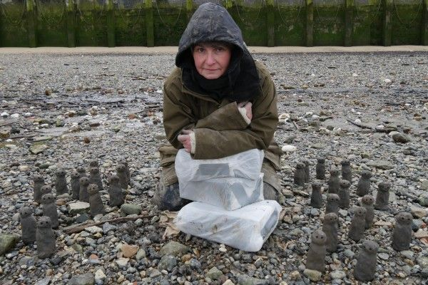 Artist Liz Crow kneels on tames foreshore in wet weather gear leaning on foam blocks looking into the camera. Small clay figures are positioned either side of her.