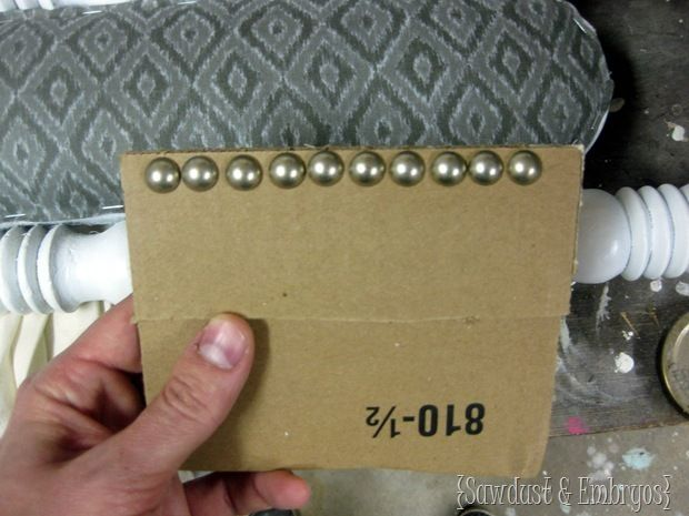 Genius tip for DIY-ing nailhead trim - use a cardboard template with slits cut evenly and slid the nails into each slit - then nail them in. Perfect spacing!