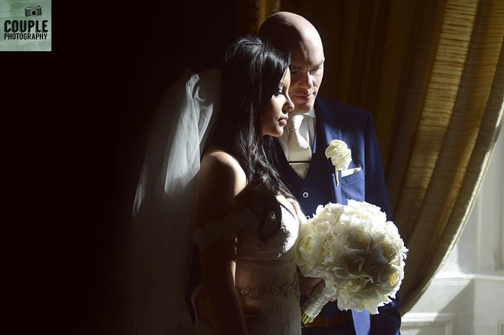 The bride & groom in the strong window light in the gold room at Cabra. Weddings at Cabra Castle photographed by Couple Photography.