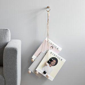 Een decoratieve hangende opberger voor je tijdschriften, all on a string. Het tijdschriftenrek bestaat uit een metalen ring met 10 naturel leren koorden met aan het eind een grote houten kraal.