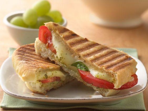 Panini Caprese:  1 panini.- paar plakjes tomaat.-  paar plakjes mozzarella.- 2 theelepels pesto.  Snijd de panini doormidden, smeer de ene helft van de panini in met pesto. Leg hier overheen de plakjes tomaat en mozzarella. Zet vervolgens het kapje van de panini er weer boven op en leg de panini onder de grill totdat de mozzarella een beetje gesmolten is.