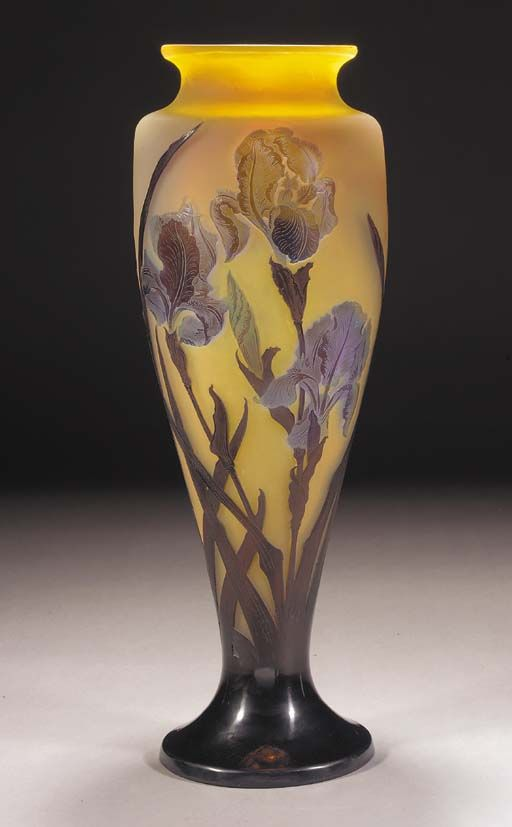 A GALLÉ CAMEO GLASS VASE - the frosted glass internally mottled with yellow and green and overlaid in violet and amethyst, etched and carved with irises and foliage, cameo mark Gallé -- 60cm. high.