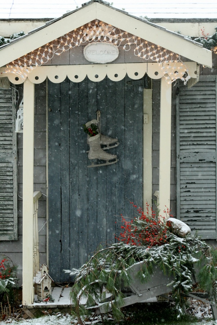 Cottage in the snow with old skates on the door and wheelbarrow of greens. Lovely.