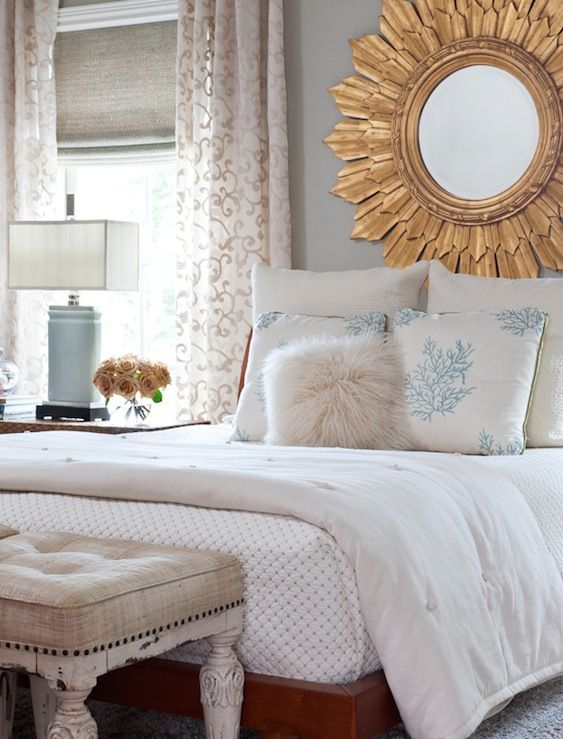 Cynthia Smiley, Chic bedroom design with gray walls paint color, cherry wood bed, gold sunburst mirror, linen tufted ottomans, linen roman shade and scroll window panels. Benjamin Moore Coastal Fog