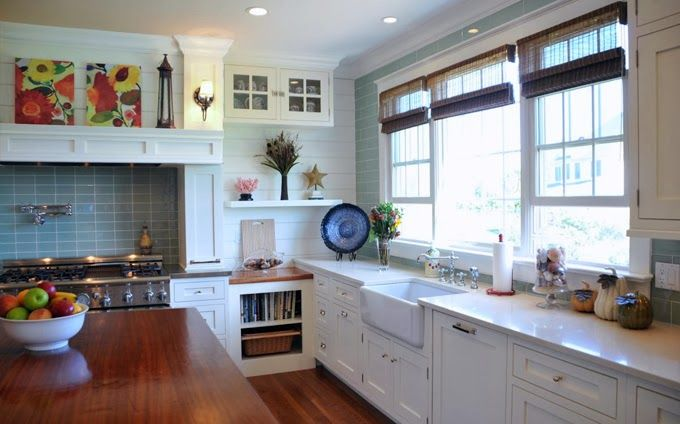 Farmhouse sink, no door on cabinet with books, decorative shelf. Love the three part window. Bright counter top.