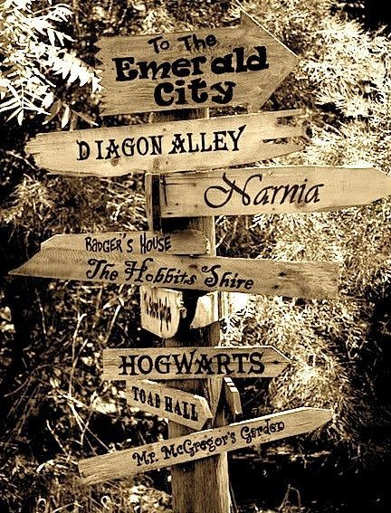 Directional sign for backyard play area.  Emerald City, Narnia, Hogwarts, Mr. MsGregor's Garden, The Hundred Acre Wood, Stars Hallow, Mad Hatters', Orchard House, Neverland, Hartfield, The Secret Garden,: