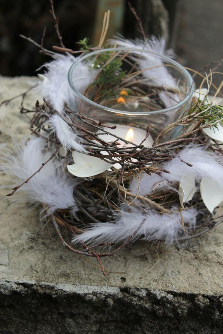 Originelle Osterdekoration mit Federn Eierschale und Kerze