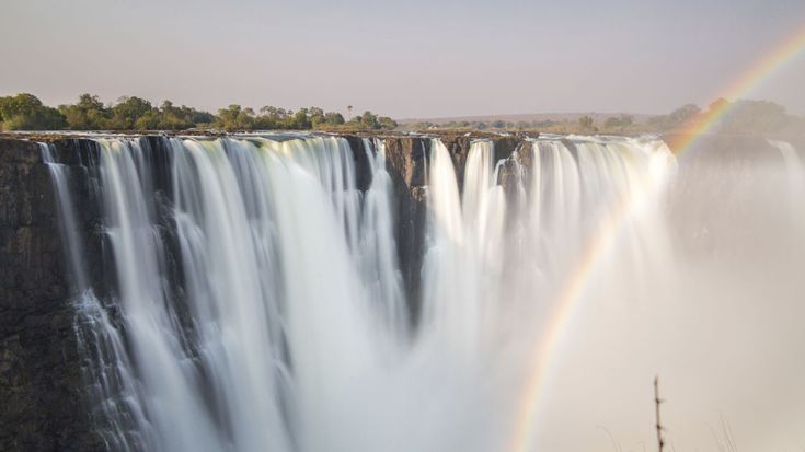"""Die Victoriafälle stürzen sich an der Grenze zwischen Sambia und Simbabwe in die Tiefe. Ihr ursprünglicher Name """"Mosi-oa-Tunya"""" bedeutet so viel wie """"donnernder Rauch"""". Seit 1989 gehört der grenzüberschreitende Nationalpark zum UNESCO-Weltnaturerbe. Nach Konflikten über die mögliche Nutzung der Wassermassen zur Energiegewinnung haben sich die beiden Anrainerstaaten heute den besonderen Schutz des Gebiets zur Aufgabe gemacht."""