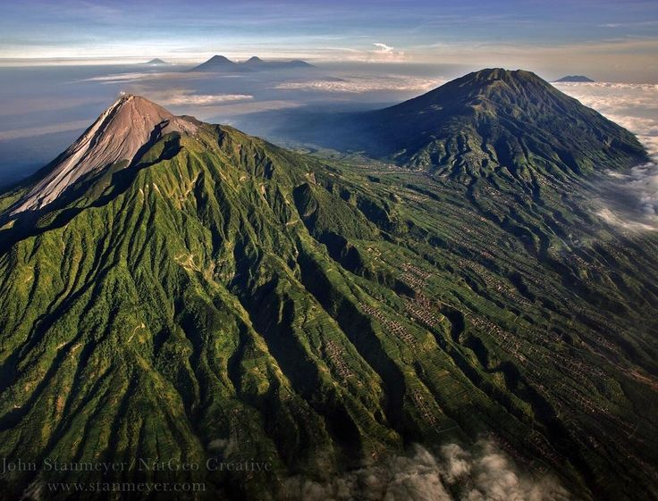 Photograph by @JohnStanmeyer Ring of Fire Mount Merapi (foreground) takes but also gives giving so much that thousands of people live directly upon its slopes embracing the rich ash this mystical volcano offers into the soil. The island of Java sits upon the Ring of Fire a line of active volcanoes that stretches across the entire archipelago. This image was from my @natgeo story #VolcanoGods a deep anthropologic project I did related to spiritual connections of volcanoes and their mystical…