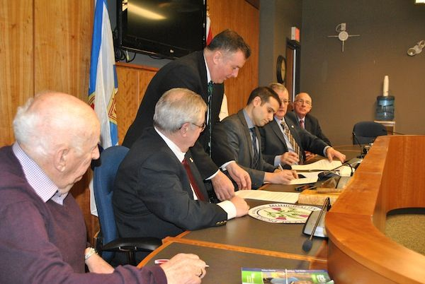 Zach Churchill, the minister of Municipal Affairs, is shown signing an agreement with the four Pictou County municipalities working toward regional government, watched by the mayors and wardens involved. The agreement provides more than $27 million over five years to help with the costs of amalgamation, if the merger is approved. CAROL DUNN – THE NEWS