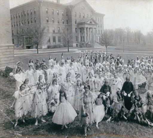 College of St. Catherine, theater students, Saint Paul, Minnesota :: St. Catherine University Students in costume are shown standing on the lawn in front of College Hall. This photograph shows the cast of the play Every Woman's Road, which was performed in the spring of 1917. The West and North sides of Derham Hall can be seen in the upper left of the picture.
