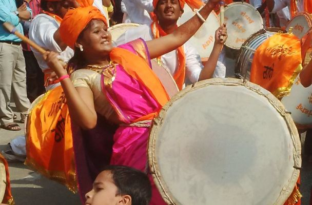 Woman playing huge drum in the Gudi Padva Carnival, India.