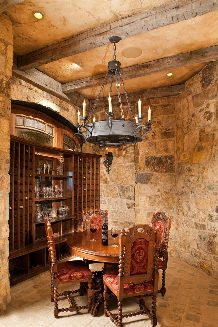 Step back in time in this Medieval inspired wine cellar with an iron chandelier and Gothic dining chairs. Exposed stone walls, floor pavers and weathered wood beams enhance the old world feel.