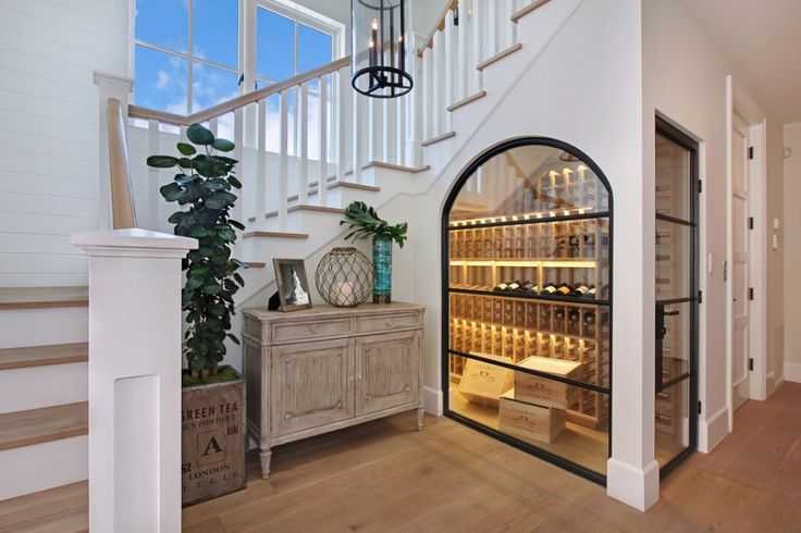 A way to use space under the stairs that I've never seen before!  Really stunning wine storage/cooler.