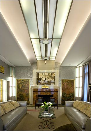 The two-story living room in the Chicago house has silver walls, a massive fireplace and two sets of panels from an Art Deco ocean liner