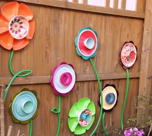 Make this DIY fence decor using supplies from the dollar store! Pick out various cups, bowls, plates and platters. Attach them together to create pretty flowers, then hang them on the fence. Use a green hose to make the stems. GREAT idea and easy to do!