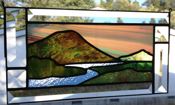 Stained glass hanger with water, mountain and sky landscape and beveled border.