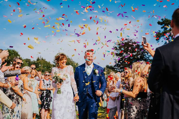 Epic confetti shot with the help of the groomsmen setting of multiple confetti canons! Amazing. Photo by Benjamin Stuart Photography #weddingphotography #confetti #groupshot #brideandgroom #justmarried #confetticanon #party