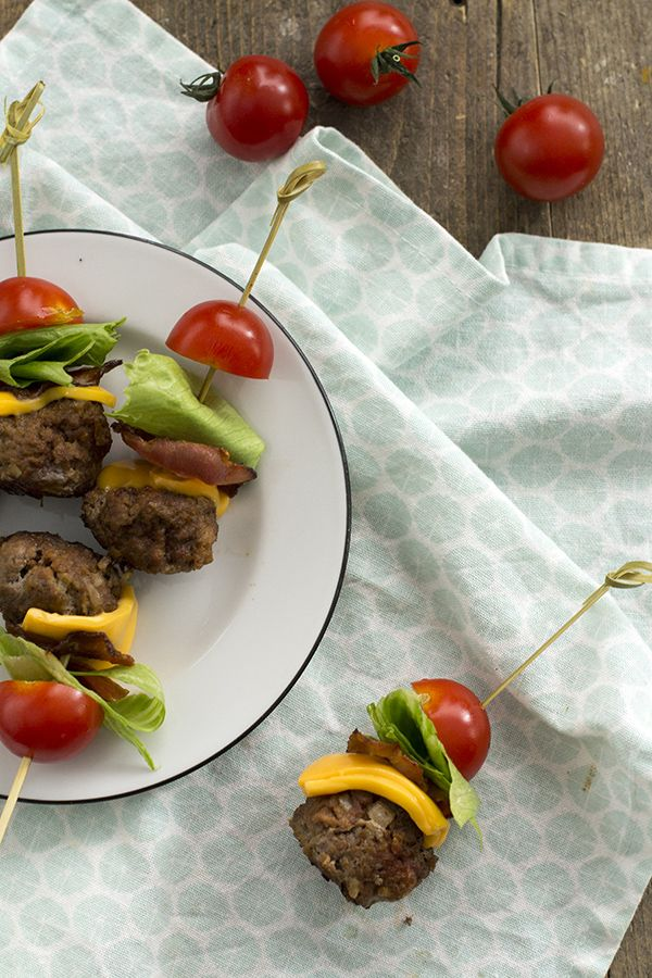 Een leuk hapje voor op een feestje: mini cheeseburger op een stokje met spek en tomaat. Alle ingrediënten van een cheeseburger, zonder broodje.