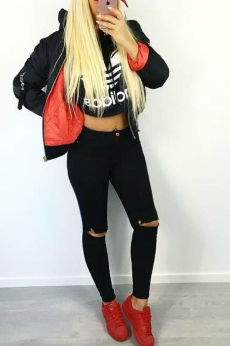 a blond teen girl wearing a casual tomboy fall winter outfit with ripped black jeans red sneakers and a bomber jacket