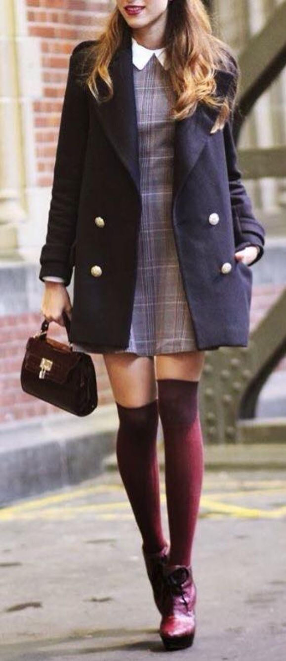A line mini dress in light purple glen plaid with white collar. Navy peacoat worn over that. She is carrying a small burgundy handbag. Platform lace-up burgundy booties with over-the-knee burgundy stockings. She looks fun, interesting and effortless. Style Planet