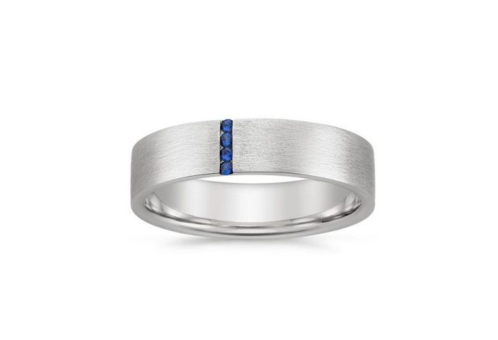 ''Mable'' Wedding Band With Vertical Round Cut Sapphires. This modern band features a thin vertical row of blue sapphires against a matte, brushed finish for a stylish look. The softened inside edge provides increased comfort. Band Width: 7 mm. 4 Blue Natural Sapphire, about 0.06cts total.