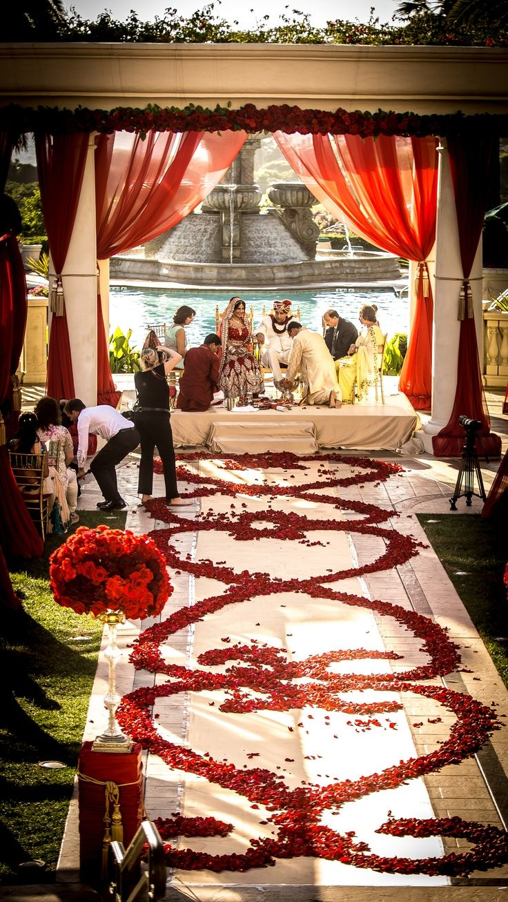 All red roses-red rose petal aisle paired with rose garlands and red drapery for this royal indian wedding. | Capriflower Weddings
