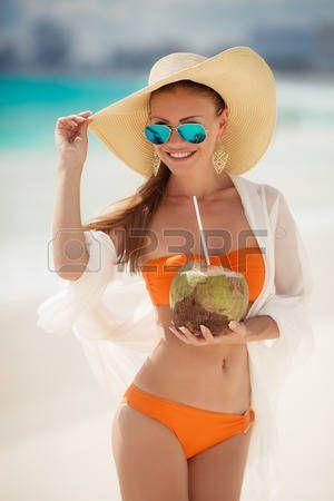 Una donna con una bella figura, bruna con lunghi capelli dritti in bikini arancione, in un grande cappello di paglia, con una sciarpa bianca trasparente luce drappeggiato dietro gli occhiali scuri in piedi su una spiaggia, bere attraverso un latte di cocco paglia. photo
