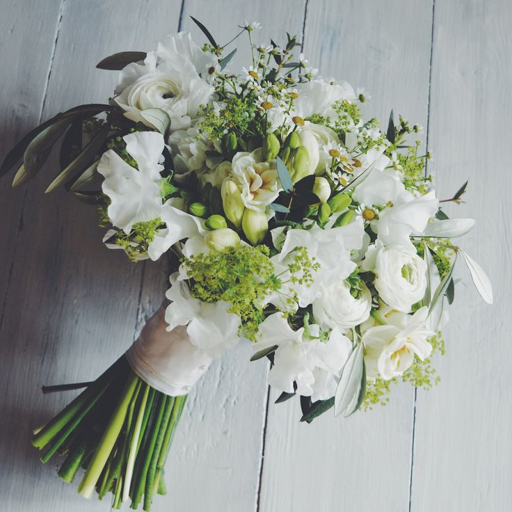 Hand tied Spring bridal bouquets in whites created by Eden Blooms Florist. Made from Sweet Pea, Rannunculus, Olive, Paperwhites, Alchimilla, Tanacetum Daisy, Freesia & Eucalyptus Parvifolia. Image by Eden Blooms Florist.