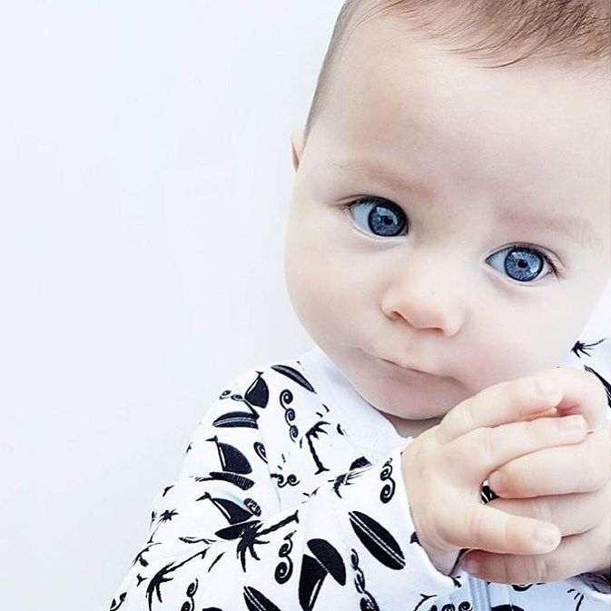 Could this little guy look any cuter in our Oakie Baby Ocean Beeeze zip up onesie. 100% gots certified organic cotton in a gorgeous gender neutral monochrome print. . . @three_mini_micks . . . . [close up image of a white infant grasping his hands together wearing a monochrome romper with a yacht and palm tree ocean print.]