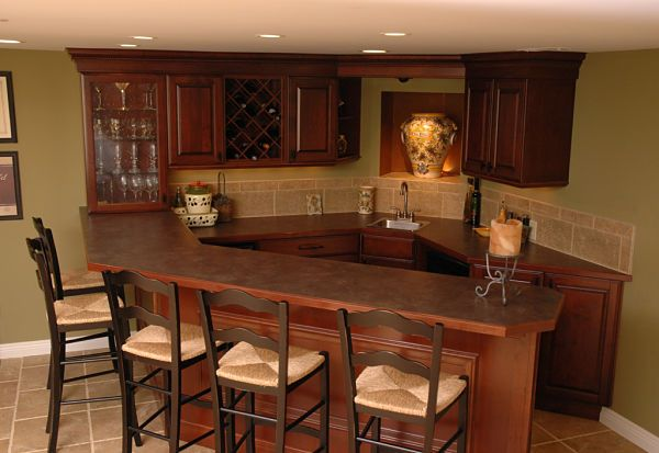 The square wall niche displays a wine cask that is a focal point in this lower level bar area. By Neal's Design Remodel.