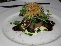 Organic fillet of beef poached in red wine enhanced lamp jus served with horseradish, watercress and shoestring potatoes