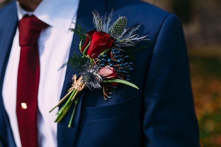 Beautiful wintery flowers make up this gorgeous buttonhole and look fab with a dark crimson tie, tie pin and navy suit. Photo by Benjamin Stuart Photography #groom #weddingflowers #buttonhole #suit