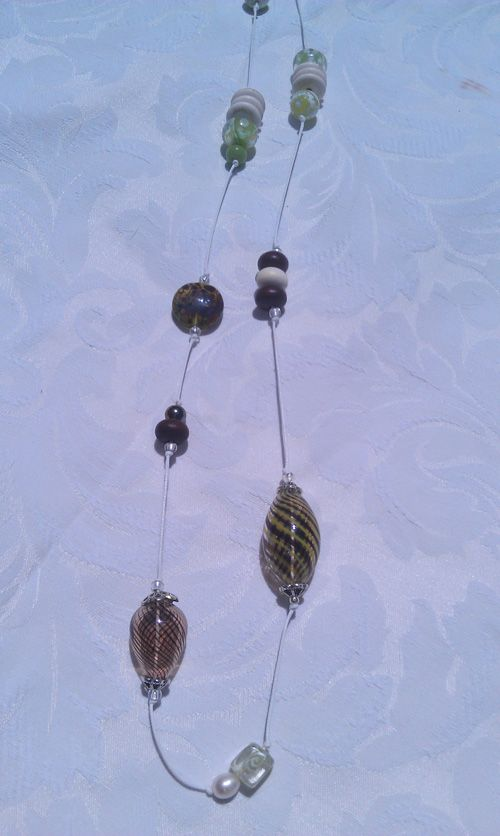 Mixed beads on waxed cotton thread, faceted agate, blown glass, wood and crystal.  Includes lampwork coin made by Wildlight Studios, a local glass artist.