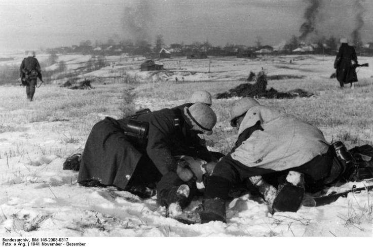 Битва под Москвой . vor Moskau November - Dezember 1941 Bergung eines Verwundeten, im Hintergrund brennende Häuser in einer Ortschaft.