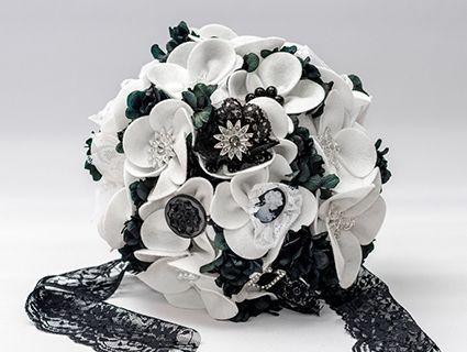 1961 Bouquet. Elaborado con 16 flores de fieltro blanco terminadas en botones negros, camafeos, hebillas y broches; que forman un ramo de cerca de cuarenta centímetros de diámetro sobre un nido de alambre y perlas. El mango, forrado en lazo de raso blanco y adornado con un lazo de encaje negro.
