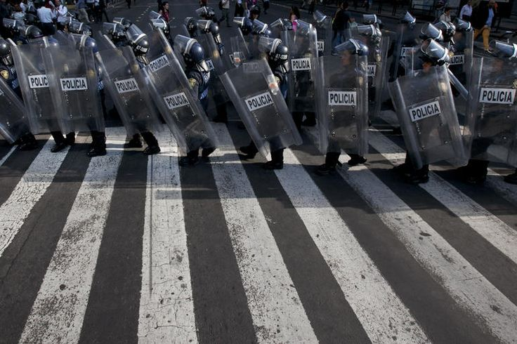 Police march in riot gear to man positions during a march commemorating the 1971 student massacre known as ''El Halconazo,'' in Mexico City, June 10, 2015. (Photo by Marco Ugarte/AP)