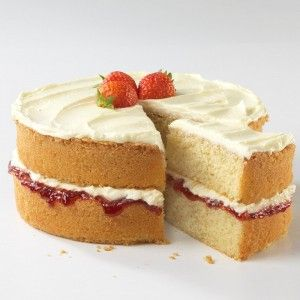 Victoria sponge with one slice removed, filled with cream and jam with strawberries on top.